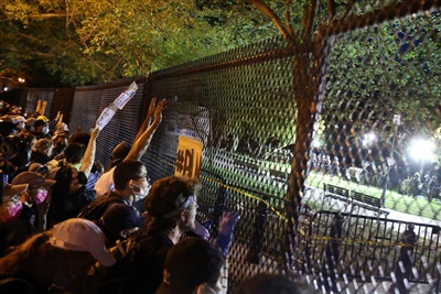 Quá 10h tối trước hàng rào bảo vệ Nhà Trắng: Người biểu tình ôn hòa, sau đó một số người tức giận ném chai nước vào cảnh sát nhưng đã được đám đông thuyết phục giữ bình tĩnh.