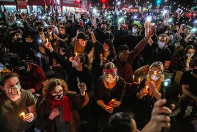 Đám đông thắp nến và mở đèn flash trên đường phố quận Brooklyn, New York