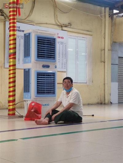 Người đàn ông cố gắng ngồi gần quạt điều hòa để tránh nóng.