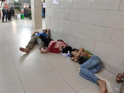 Nhiều người nhà bệnh nhân tại Bệnh viện Bạch Mai nằm ngủ ngay dưới nền nhà tại các hành lang, gầm cầu thang của bệnh viện để đỡ nóng.