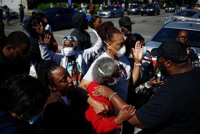 Mẹ của McAtee và nhiều người xung quanh cùng cầu nguyện cho người đàn ông vắn số (Ảnh: NY Times)