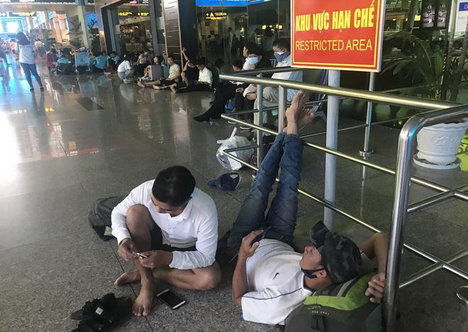 Một nam hành khách nằm chờ tại sảnh ga nội địa Tân Sơn Nhất.