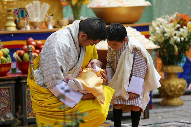Tiểu hoàng tử ngoan ngoãn trong vòng tay của vua cha.