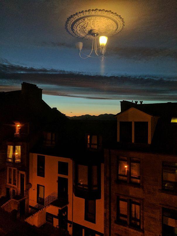 14. Ánh sáng của chiếc đèn chùm phản xạ lên cửa kính, làm cho cái trần nhà trông như thể đang lơ lửng giữa bầu trời.