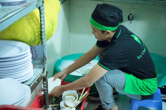 Hồ Văn Cường rửa bát phụ mẹ nuôi.