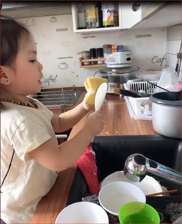 Bé gái vừa rửa bát vừa hát ca khúc yêu thích.