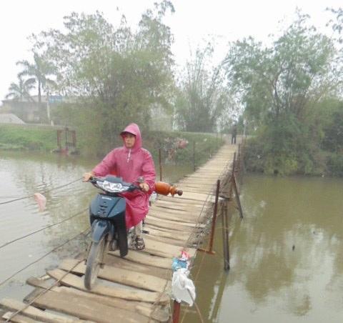 Không có lan can, mỗi bên thành cầu được giăng ba sợi sắt 8. Người đi qua cầu chỉ cần bất cẩn một chút là thụt chân xuống sông.