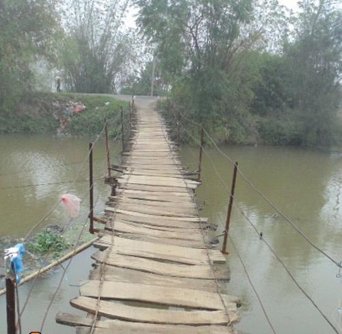 """Cho đến nay, cây cầu """"ma ám"""" đã hơn 50 tuổi nhưng vẫn chỉ được làm tạm bợ, lát bằng gỗ và không có lan can, rất nguy hiểm."""