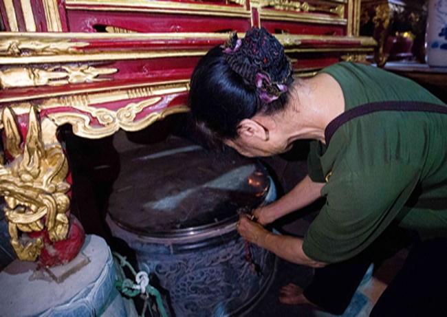Trưởng vãi Ngô Thị Hoa cẩn thận mở nắp che trên miệng giếng. (Ảnh Hữu Thắng)