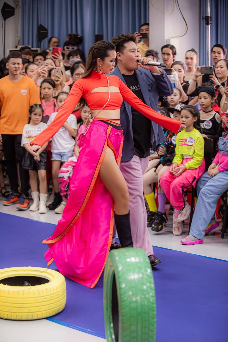 Diện trang phục crop top màu cam neon nổi bật, siêu mẫu Hà Anh tự tin khoe chân dài khi thị phạm sải bước động viên tinh thần các người mẫu đến casting.