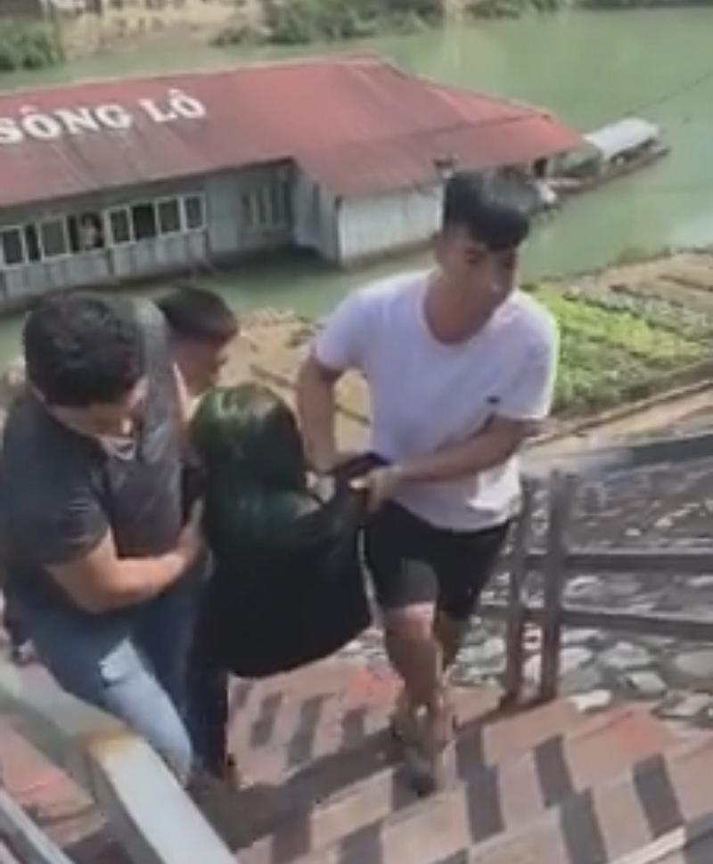 Cô gái được 3 nam thanh niên khiêng từ dưới sông lên (Ảnh cắt từ clip).
