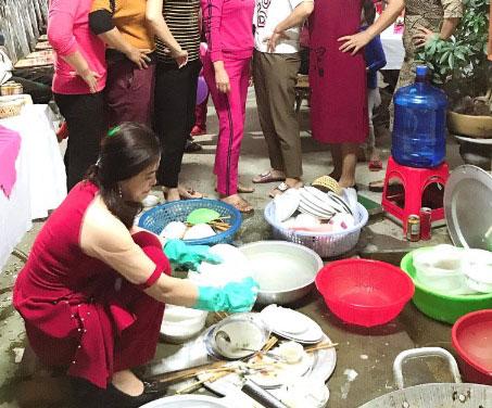 Hình ảnh cô dâu hì hục rửa chén bát khi xung quanh là nhiều cô dì đang đứng quan sát, chỉ trỏ.