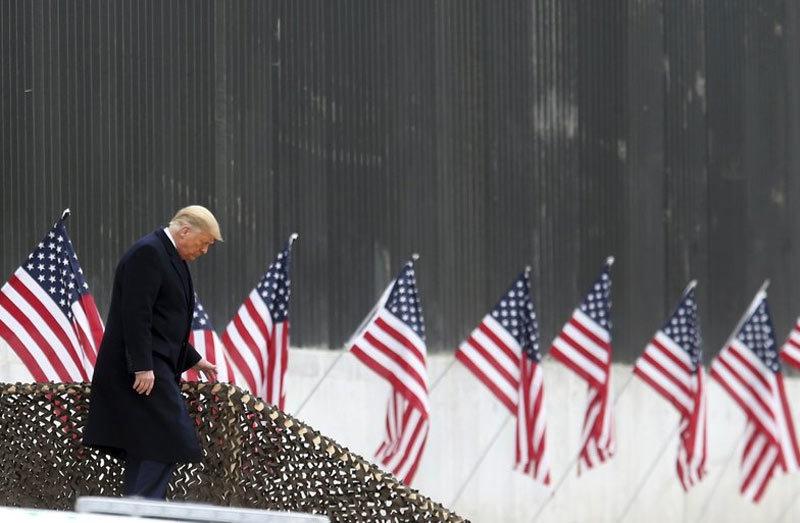 Tổng thống Donald Trump bước xuống các bậc thềm trước khi có bài phát biểu gần một đoạn tường biên giới ngăn cách Mỹ và Mexico ngày 12/1 ở Alamo, Texas. Ảnh: AP