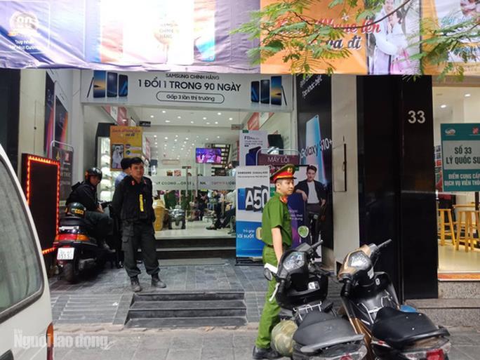 Lực lượng cảnh sát khám cửa hàng điện thoại Nhật Cường tại số 33 phố Lý Quốc Sư của ông chủ Nhật Cường Bùi Quang Huy - Ảnh: Huy Thanh