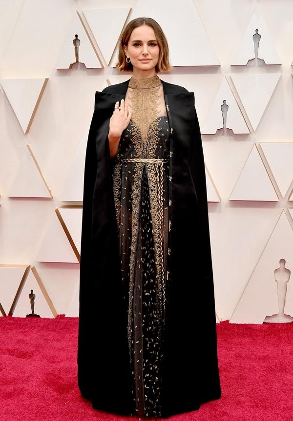 Natalie Portman kín đáo nhưng lại đầy sang trọng, quyền lực khi diện thiết kế của nhà mốt Dior.Điểm nhấn chính của thiết kế này nằm ở các họa tiết thêu thủ công màu vàng gold và chiếc thắt lưng mạ vàng độc đáo. Đi cùng chiếc đầm là áo choàng vải satin cao cấp có thêu tên các nữ đạo diễn tài năng nhưng không được đề cử trong giải Oscar 2020.