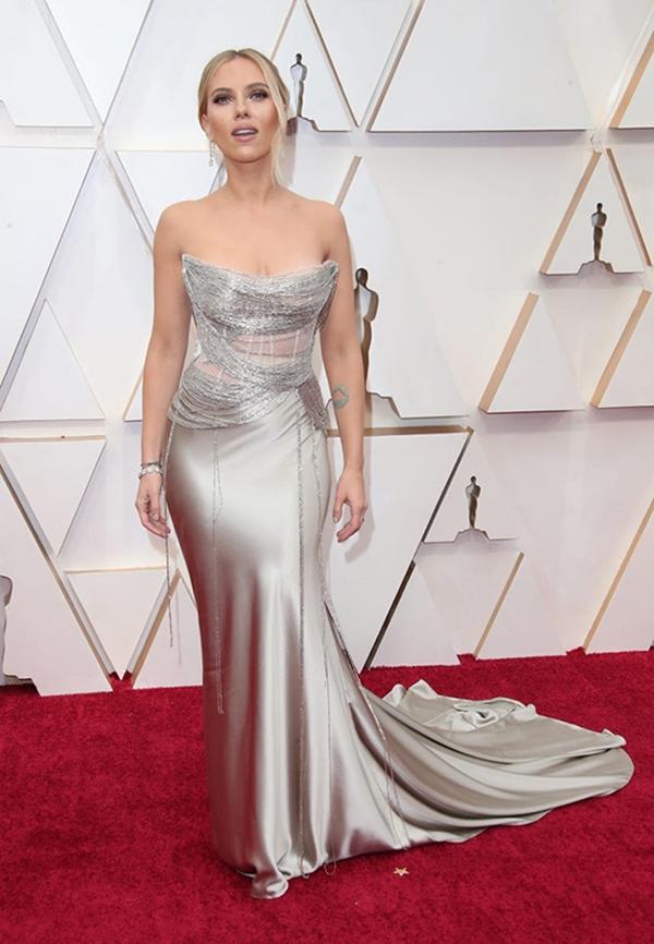 Scarlett Johansson lộng lẫy và đầy gợi cảm nhờ bộ đầm cúp ngực màu bạc ánh kim của Oscar de la Renta. Cô kết hợp trang phục cùng trang sức hoa tai kim cương 27 cara Forevermark trị giá 2,5 triệu USD.