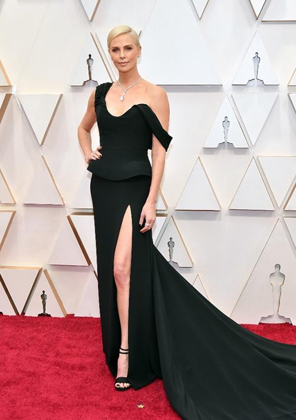 Charlize Theron tôn khéo đôi chân thon dài cùng bờ vai trần mảnh mai khi chọn đầm đen xẻ đùi của Dior Haute Couture. Cô kết hợp bộ cánh cùng sandal đồng điệu. Vòng cổ kim cương đến từ thương hiệu Tiffany & Co chính là nét chấm phá giúp vẻ ngoài của diễn viên trở nên hoàn hảo.