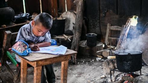 24h qua ảnh: Cậu bé ngồi học cạnh bếp lửa trong nhà