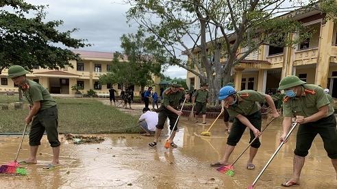 Công an, bộ đội giúp người dân dọn bùn sau lũ lụt ở Quảng Bình