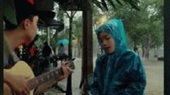 Dân mạng truy tìm danh tính cô gái Huế mặc áo mưa ngồi đàn hát giữa trời mưa ngập lụt