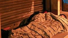 Người vô gia cư ở Hà Nội co ro, trùm áo mưa ngủ trên vỉa hè trong đêm mưa rét