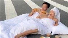 Cặp đôi nhận 'gạch đá' khi diện trang phục gây sốc và 'biến lòng đường thành chiếc giường' để chụp ảnh cưới