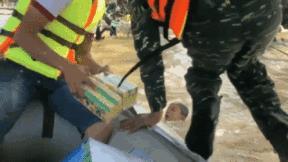 Người đàn ông nhảy xuống, giúp bé trai đang vật lộn giữa dòng nước lũ