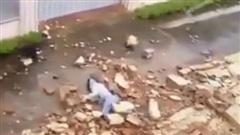 Clip: Kinh hoàng cảnh mảng tường bất ngờ đổ sập trong cơn mưa, đè lên cô gái đi bộ khiến nạn nhân nằm bất động