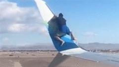 Người đàn ông thản nhiên 'chời đùa' trên cánh may bay khi sắp khởi hành