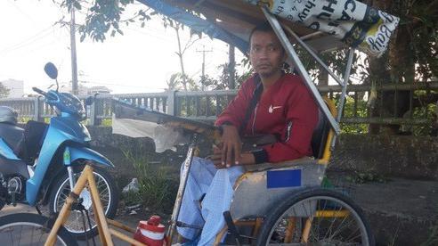 CLIP: Người đàn ông ngồi xe lăn bán vé số đang hoại tử đôi chân