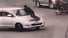 Bất chấp có người đu trên nắp capo, nữ tài xế vẫn nhấn ga chạy xe băng băng trên đường
