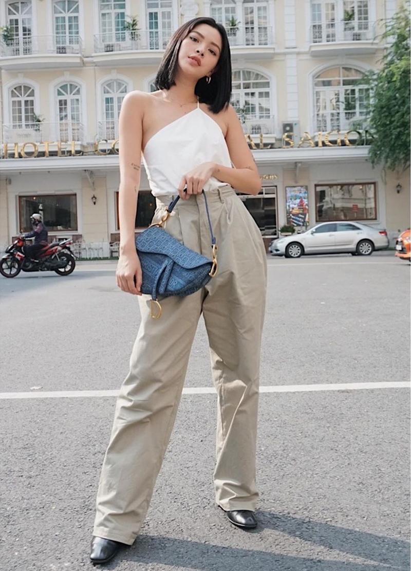 Tú Hảo 'thả dáng'nuột nà trên phố trong bộ đồ kết hợp quần kaki và áo lệch vai, có điểm sáng là chiếc túi Saddle phiên bản mới của Dior.