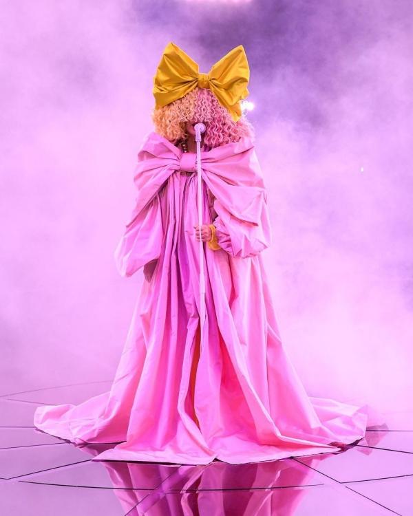Sia mặc dù không đi thảm đỏ BBMAs nhưng vẫn khiến dân tình bàn tán không ngừng với tạo hình nổi bật, chói lóa hết sức, từ chiếc nơ vàng trên mái tóc xù mì che kín mặt cùng outfit màu hồng ngọt ngào cũng lấy cảm hứng từ nơ.