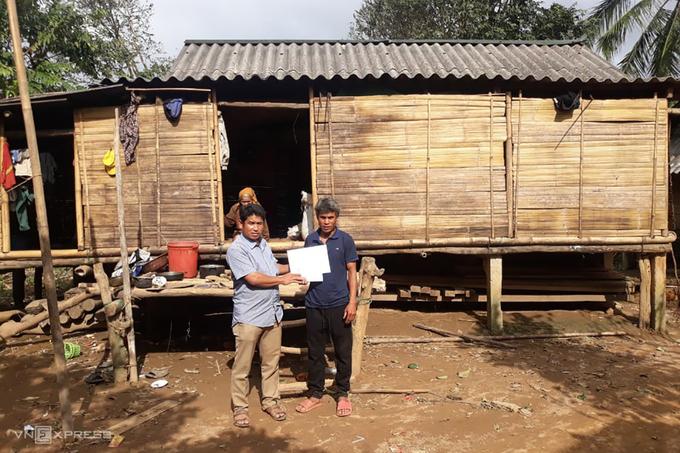 Ông Ăm Diệu nhận 10 triệu đồng từ nhà từ thiện, sau khi tìm cách trả lại số tiền bỏ quên trong áo quần cứu trợ. Ảnh: VNE.