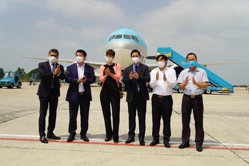 Tổng lãnh sự và Giám đốc Thương mại Vương quốc Anh tại Việt Nam Emily Hamblin và Thứ trưởng Bộ Y tế Trương Quốc Cường cùng đại diện công ty nhập khẩu tại sân bay đón lô vắcxin. (Ảnh: TTXVN phát)
