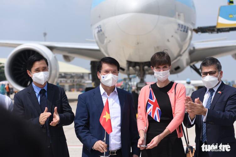 Thứ trưởng Bộ Y tế Trương Quốc Cường (cầm cờ Việt Nam), đại diện lãnh sự quán Anh tại TP.HCM (cầm cờ Anh) và đại diện công ty nhập khẩu tại sân bay đón lô vắcxin - Ảnh: Duyên Phan
