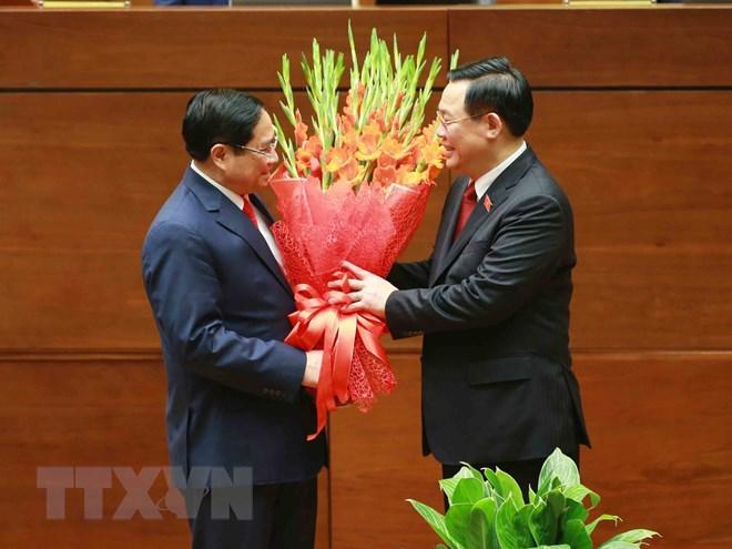 Chủ tịch Quốc hội Vương Đình Huệ tặng hoa chúc mừng Thủ tướng Phạm Minh Chính. (Ảnh: Phương Hoa/TTXVN)