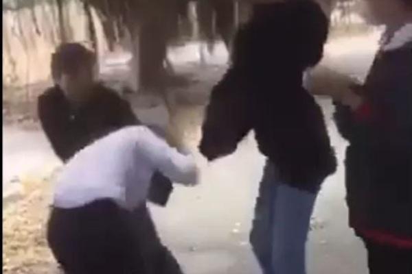 Một em mang áo khoác đen dùng mủ bảo hiểm đánh vào vùng đầu nữ sinh. Ảnh cắt từ clip