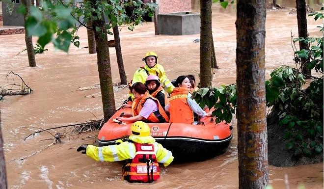 Lực lượng cứu hộ giải cứu những người bị mắc kẹt trong lũ lụt ở tỉnh Hà Nam. (Ảnh: Tân Hoa Xã)