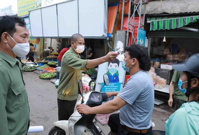 Ban Quản lý chợ đầu mối Minh Khai tổ chức đo thân nhiệt cho người dân khi đến chợ. Ảnh: TTXVN