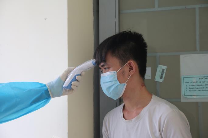 Nhân viên y tế đo thân nhiệt cho người dân đang cách ly Ảnh: Giang Nam
