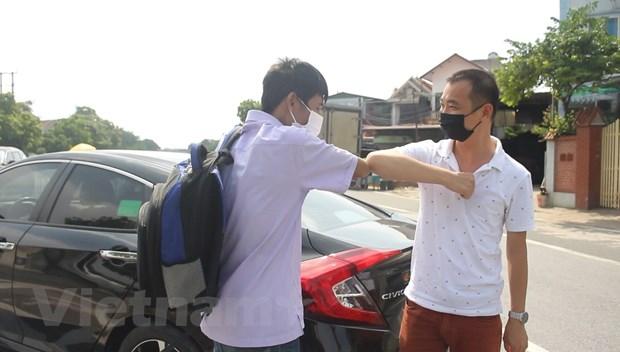 Anh Nguyễn Bình Minh (phải), người sáng lập 'Những chuyến xe yêu thương' tiếp sức cho bệnh nhân về quê mùa dịch. (Ảnh: Minh Anh/Vietnam+)
