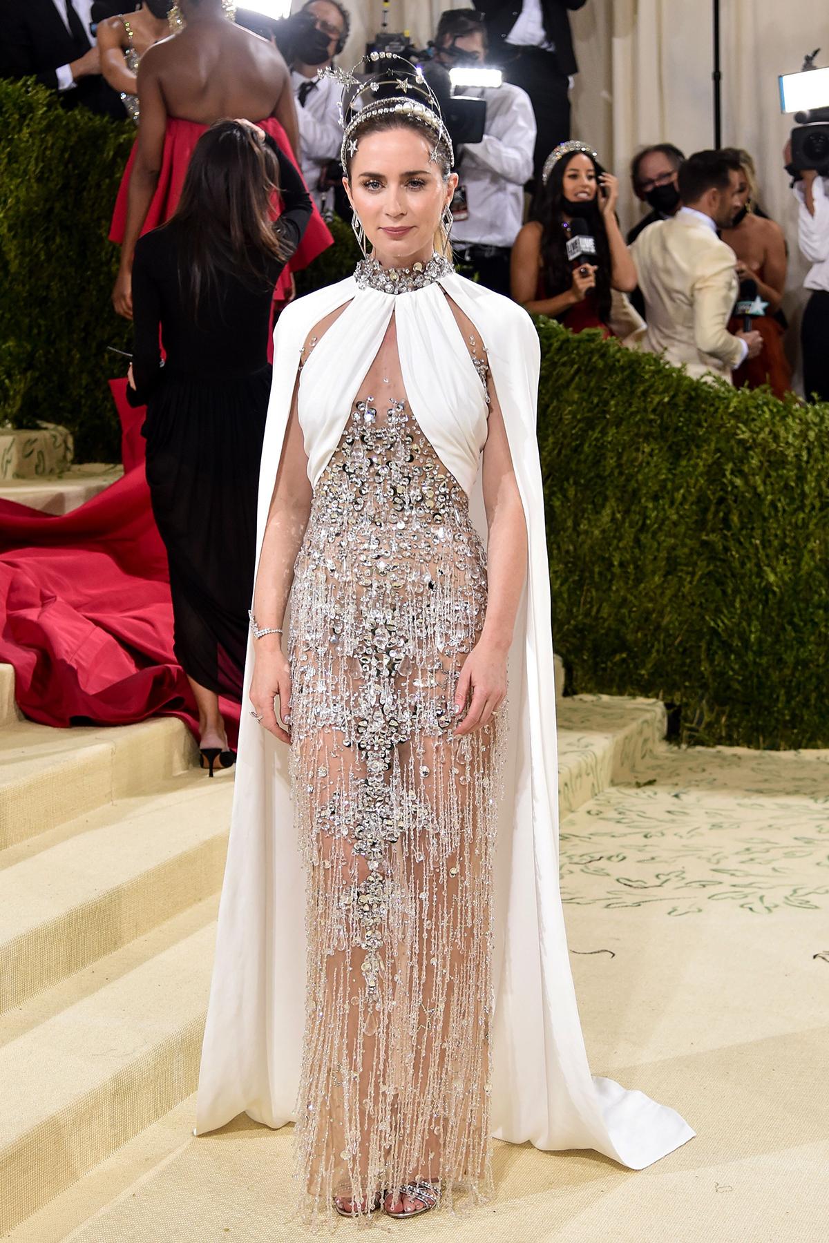 Emily Blunt cũng tạo ấn tượng với đầm màu bạc xuyên thấu kết hợp áo choàng trắng phong cách nữ hoàng.