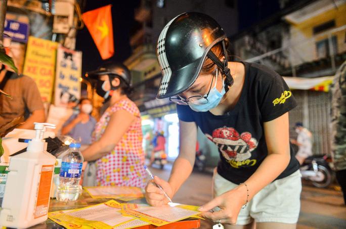 Người dân xem menu danh sách các loại bánh của cửa hàng và ghi những thông tin từng loại bánh cần mua