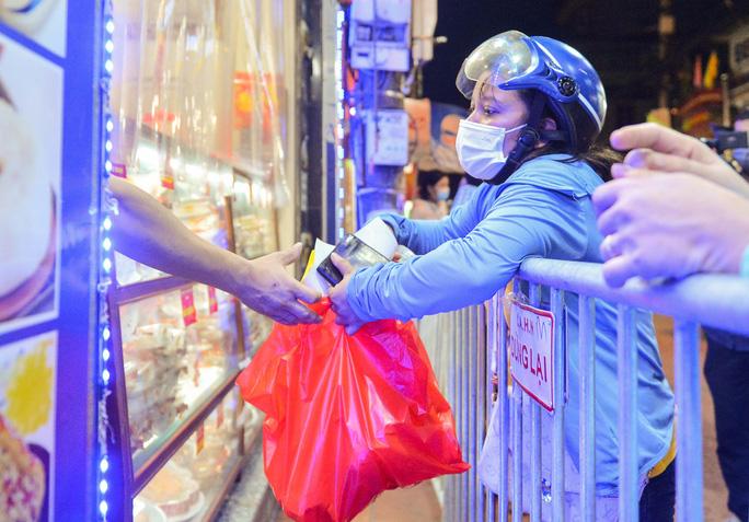 Nhân viên cửa hàng đang đưa bánh chung thu qua lớp vách ngăn bằng túi nilon cho người dân