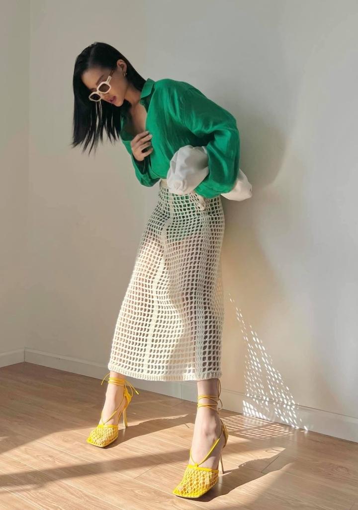 Khánh Linh kết hợp sơ mi xanh kén da cùng chân váy lưới màu trắng ivory. Nữ người mẫu thể hiện thẩm mỹ tinh tế khi khéo kết hợp cùng giày cao gót màu vàng mustard. Loạt phụ kiện kính mắt và túi xách màu trắng tạo nên một tổng thể vừa vặn.