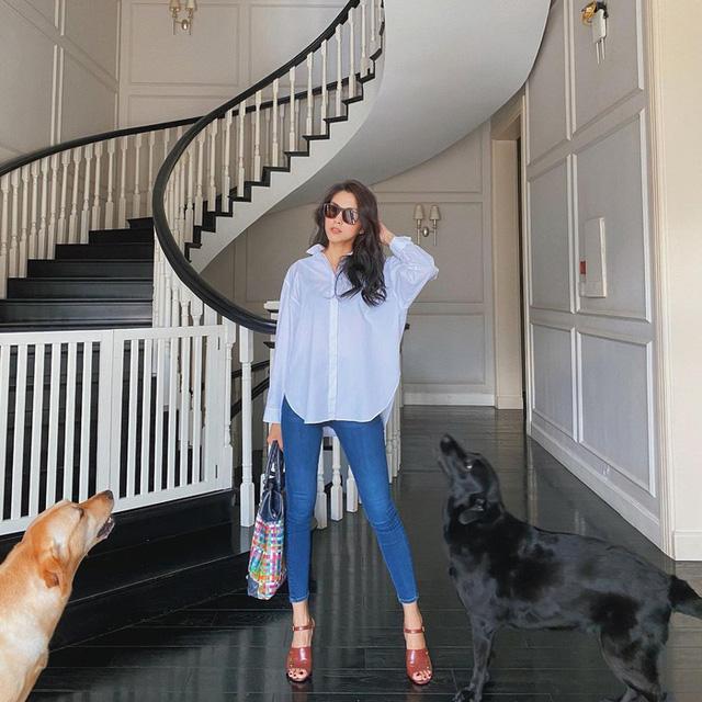 Ở outfit khác, nàng ngọc nữ phối sơmi trắng oversize buông ngoài quần skinny jean và cũng làm nổi bật set đồ với phụ kiện như kính, túi xách sặc sỡ và xăng đan.