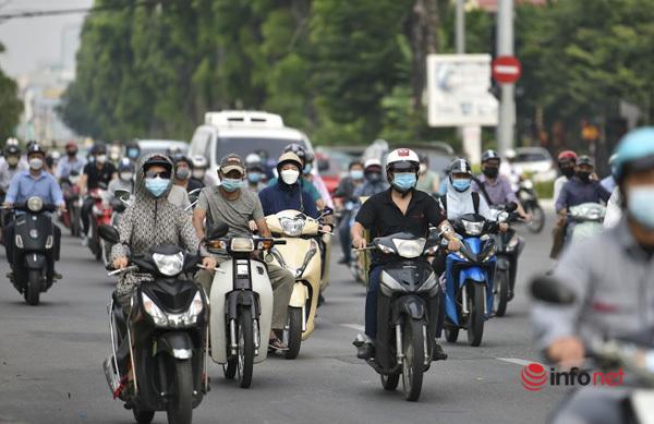 Nhiều người đi xe máy tìm cách chen qua hàng ô tô đang nối đuôi nhau.