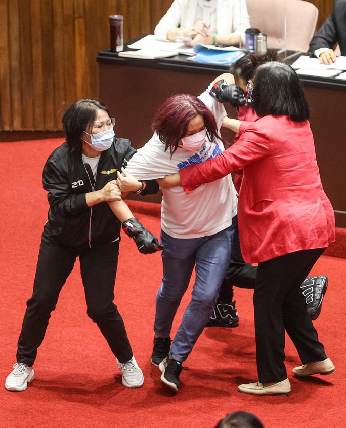 Bà Chen với mái tóc nhuộm màu tím, mặc áo phông trắng, quần jean màu xanh và đeo găng tay màu đen. Ảnh: CNA