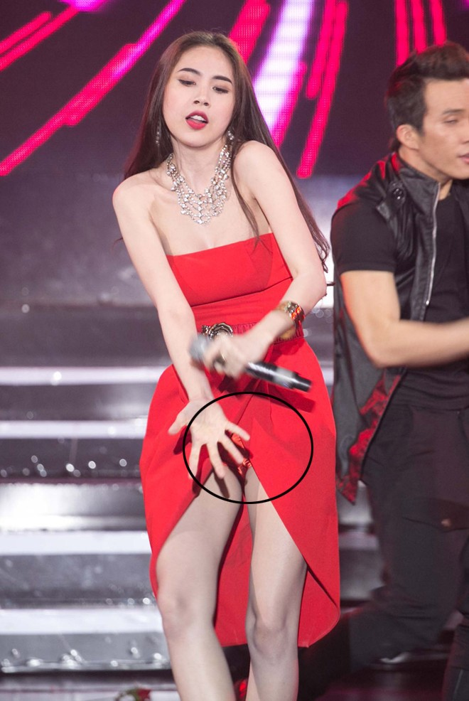 Chiếc váy xẻ tà quá cao khiến Thủy Tiên phải loay hoay che chắn khi đang biểu diễn.
